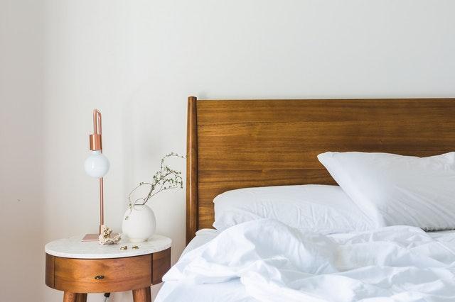 Posteľ s dreveným rámom a nočným stolíkom