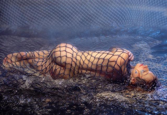 Nahá žena zamotaná v rybárskej sieti