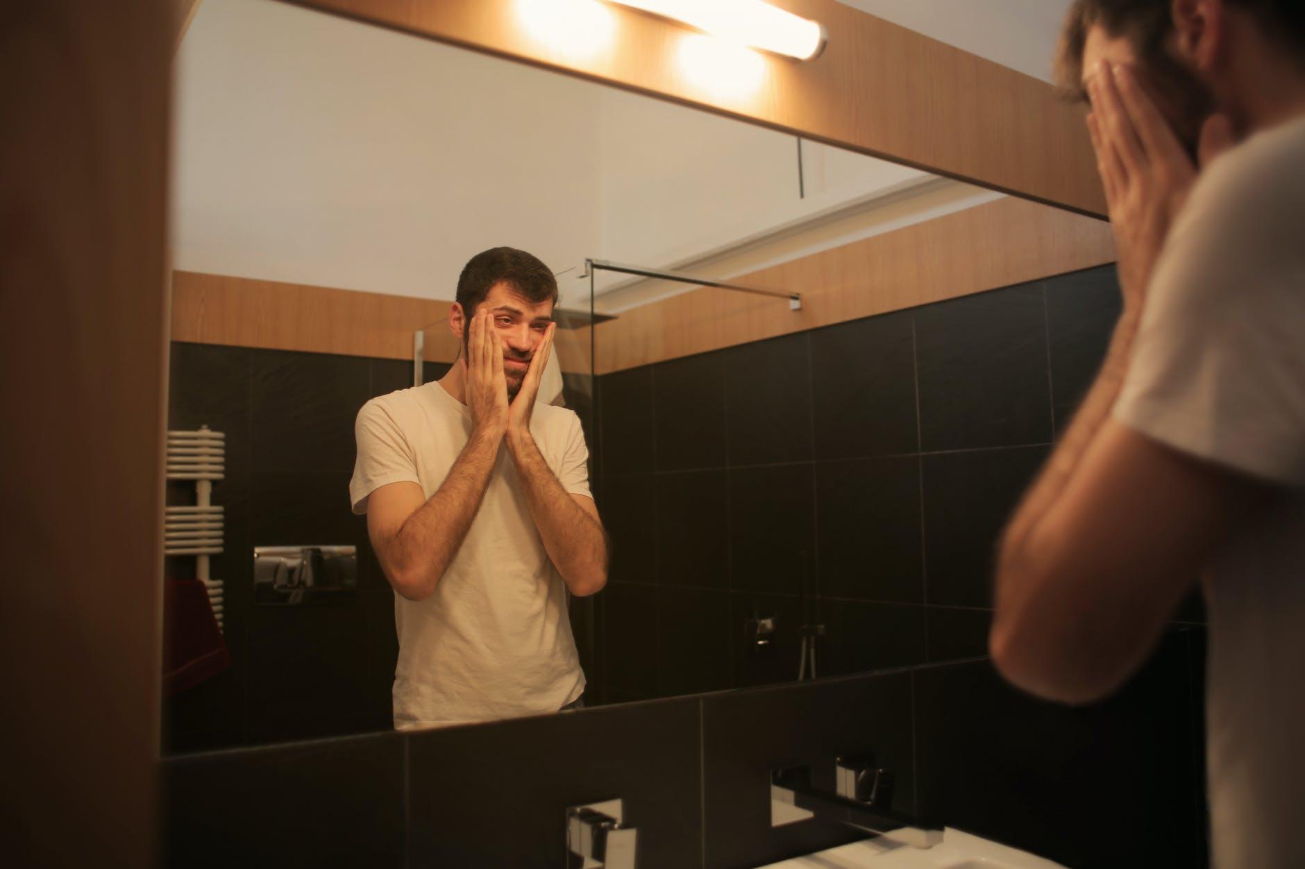 muž pozerá do zrkadla