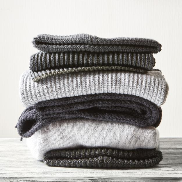 stack-gray-woolen-knitted-sweaters-white-surface_338799-2111